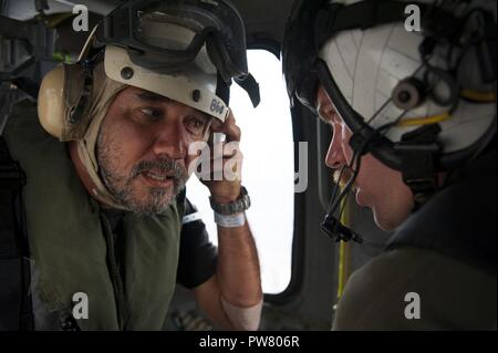 CARIBBEAN SEA (Sept. 29, 2017) Thierry Rolle, a resident of French Guadalupe, speaks with Naval Aircrewman (Helicopter) 2nd Class Brandon Larnard on an MH-60S Sea Hawk helicopter, attached to the Helicopter Sea Combat Squadron 22 (HSC-22), prior to departing the amphibious assault ship USS Wasp (LHD 1) en route to the island of Guadalupe.  Rolle and another passenger were rescued by HSC-22 personnel after their private aircraft crashed into the water off the coast of Dominica on Sept. 28. Wasp is currently participating in humanitarian relief efforts in the Caribbean Sea following the landfall - Stock Photo