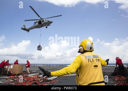 CARIBBEAN SEA (Sept. 28, 2017) Aviation Boatswain's Mate (Handling) 2nd Class Fernando Hinostroza directs an MH-60S Sea Hawk as it drops supplies transferred from the fast combat support ship USNS Supply (T-AOE 6) onto the flight deck of the amphibious assault ship USS Kearsarge (LHD 3) during a replenishment-at-sea for continuing operations in Puerto Rico. Kearsarge is assisting with relief efforts in the aftermath of Hurricane Maria. The Department of Defense is supporting FEMA, the lead federal agency, in helping those affected by Hurricane Maria to minimize suffering and is one component o - Stock Photo