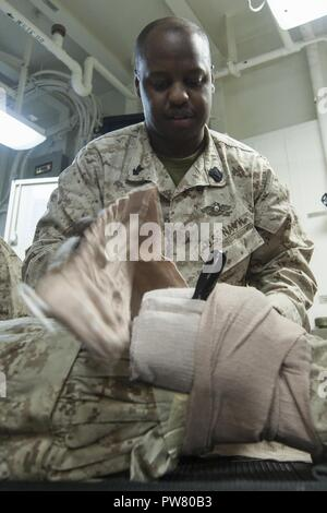 5TH FLEET AREA OF OPERATIONS (Sept. 28, 2017) Hospital Corpsman 2nd Class Talmadage Barnett, a native of Lumberton, North Carolina, assigned to the medical department aboard the amphibious assault ship USS America (LHA 6), bandages a patient's leg in the main battle dressing station during a mass casualty drill. America is the flagship for the America Amphibious Ready Group and, with the embarked 15th Marine Expeditionary Unit, is deployed to the U.S. 5th Fleet area of operations in support of maritime security operations to reassure allies and partners and preserve the freedom of navigation a - Stock Photo