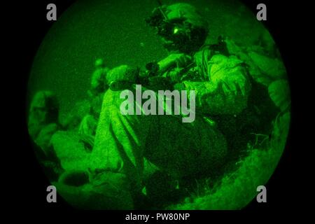 A U.S. Marine with Regimental Surveillance & Target Acquisition Company (RSTAC), 1st Marine Division, calls for radio assistance during a night insert at Fort Irwin, Calif., Oct. 1, 2017. RSTAC is an experimental company designed to build proficiency in scout sniper operations for service level exercises. - Stock Photo