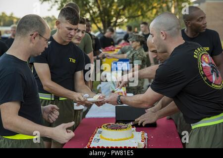 U.S. Marines with 2nd Transportation Support Battalion (TSB), 2nd Marine Logistics Group, pass out cake during the third annual reactivation ceremony of 2nd TSB on Camp Lejeune, N.C., Oct. 2, 2017. 2nd TSB hosted a battalion run to increase unit cohesion and provided cake and beverages to the Marines in attendance. - Stock Photo