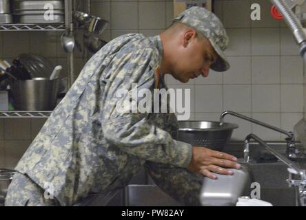 U.S. Army Reserve Pvt. Joel Garcia, a cargo specialist assigned to the 390th Sea Port Operations Company, 166th Regional Support Group, 1st Mission Support Command out of Ceiba, Puerto Rico assist with the mobile kitchen trailer team with washing dishes, Oct. 3, 2017. Garcia is proud to help support those who are out helping Hurricane Maria relief efforts. - Stock Photo