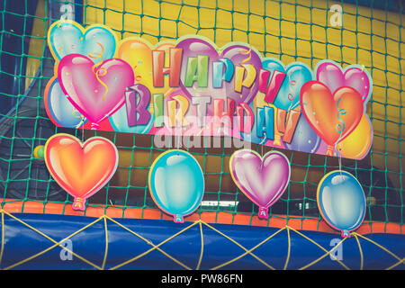 Birthday decoration with colorful inscription happy birthday and balloons in children game room background. - Stock Photo