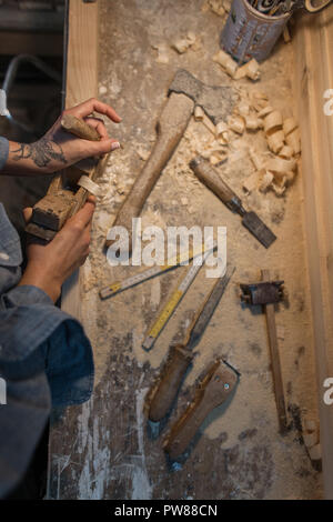 Female hands with tattoos make a wooden product in the workshop. View from above - Stock Photo