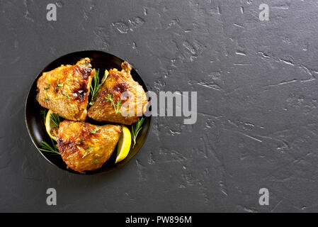Grilled chicken thighs on plate over black background with copy space. Top view, flat lay - Stock Photo