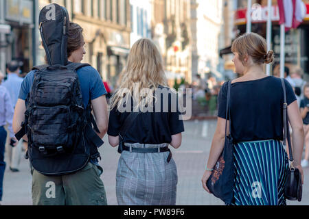 RIGA, LATVIA - JULY 26, 2018: A man and two women walk along the streets of the city. View from the back. - Stock Photo