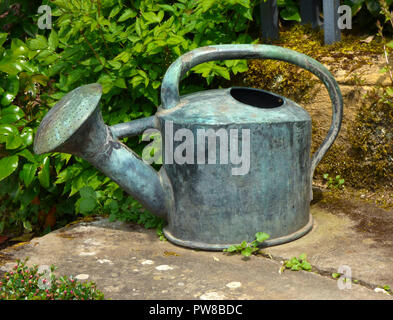 Old Victorian weathered copper watering can on a stone step at National Trust Hidcote Manor Gardens, England, UK - Stock Photo