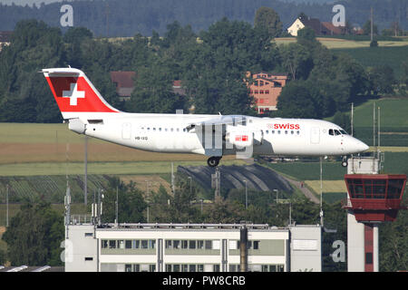 Swiss International Air Lines Avro RJ100 (old livery) with registration HB-IXQ on short final for runway 34 of Zurich Airport. - Stock Photo