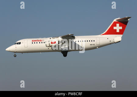 Swiss International Air Lines Avro RJ100 (old livery) with registration HB-IXQ on short final for runway 14 of Zurich Airport. - Stock Photo
