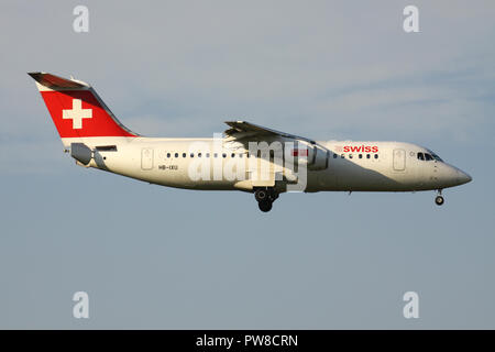 Swiss International Air Lines Avro RJ100 (old livery) with registration HB-IXU on short final for runway 14 of Zurich Airport. - Stock Photo