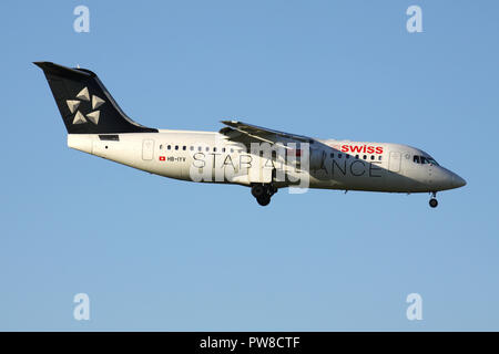 Swiss International Air Lines Avro RJ100 in Star Alliance livery with registration HB-IYV on short final for runway 14 of Zurich Airport. - Stock Photo