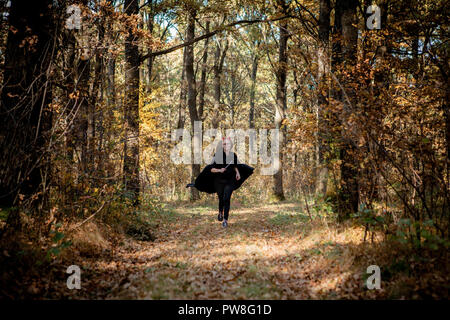 Halloween daemon with a knife runs through the woods. - Stock Photo