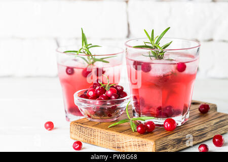 Cocktail with cranberry, vodka, rosemary and ice. - Stock Photo