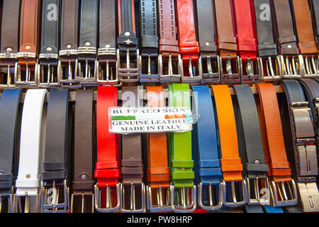 Leather belts for sale at the San Lorenzo street market in Florence,Tuscany,Italy - Stock Photo