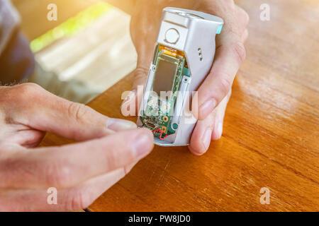 Man hands fixing modern vaporizer e-cig gadget to vape e-liquid. Maintenance of electronic equipment mech mod vaping device. Vaper device repair servi - Stock Photo