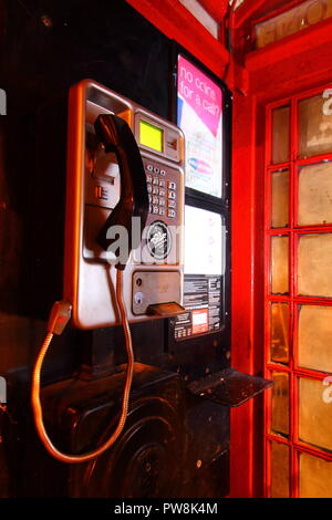 A BT public payphone inside a UK Red Telephone Box - Stock Photo