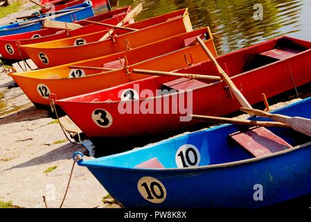 Colourful Rowing Boats Marked with Numbers Tied to Lakeside - Stock Photo