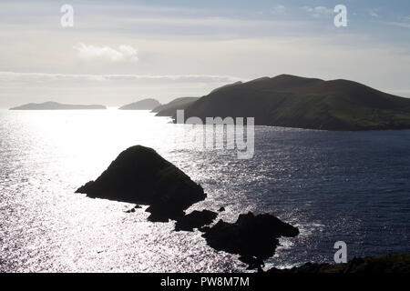 Late day ocean sunlight on the west coast of Ireland's Dingle Peninsula gives a silhouette look to the Blasket Islands off the shore from Dunmore Head - Stock Photo
