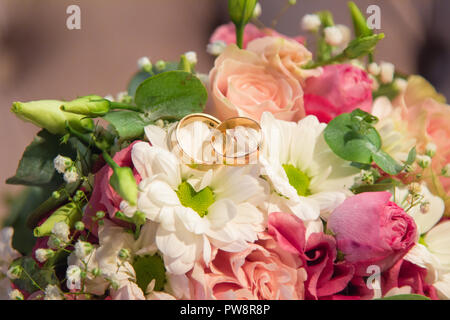 Wedding Rings on beautiful natural flowers bouquet - Stock Photo