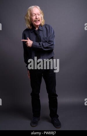 Senior businessman with mustache against gray background - Stock Photo