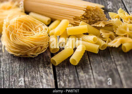 Various types of italian pasta on old wooden table. - Stock Photo