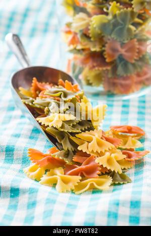 Farfalle pasta. Colorful italian pasta in scoop. - Stock Photo