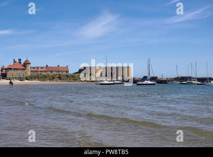 Looking North towards the Harbour at Beadnell Bay, with people Paddling in the Sea, and Yachts anchored next to the Breakwater, Northumberland, Englan - Stock Photo