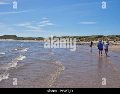 Women Paddling in the shallow clear water, on holiday at the beach at Beadnell Bay in Northumberland, England, UK - Stock Photo