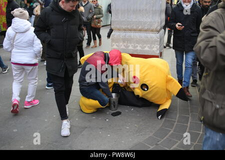LONDON, UK - February 16, 2018: Exhausted street artist next to his fancy dress counting hard earned money, people walking and looking to him. - Stock Photo