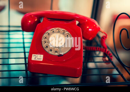 A bright red old telephone for sale at an antique store in Sheffield - Stock Photo