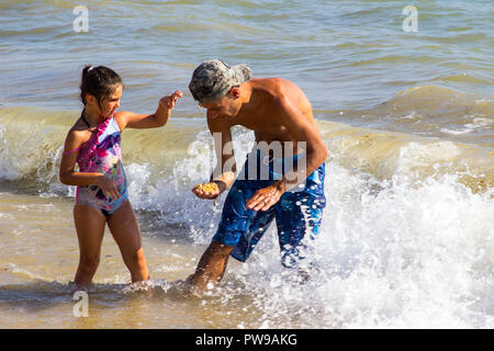 29 September 2018 A young father and young daughter play together in the surf on a beach in Albuferia on the Algarve in Portugal on a beautiful sunny  - Stock Photo