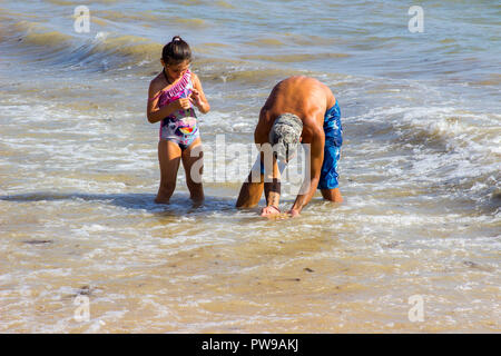 29 September 2018 A father and young daughter play together in the surf on a beach in Albuferia on the Algarve inPortugal on a beautiful sunny afterno - Stock Photo