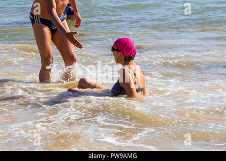 29 september 2018 A man with outstretched hand to help a lady who has fallen been swept of her feet by the breaking waves on a beach in Albuferia Port - Stock Photo