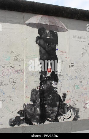 Section of East Side Gallery - Berlin Wall covered in graffiti and stencil art of boy and girl kissing under an umbrella - Stock Photo