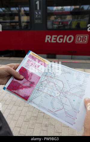 Potsdam, Berlin, Germany: 18th August 2018: Tourist looking at Marco Polo Guide and Public transport map - Stock Photo