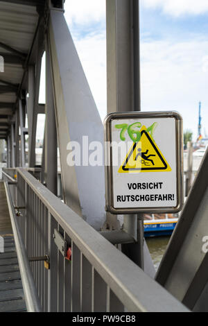 Warning sign on a pedestrian bridge not to Slip and Fall with scrawled green graffiti lettering - Stock Photo