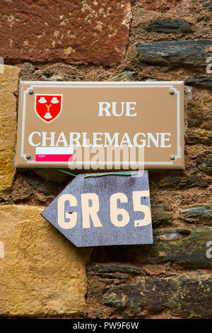 Sign on Rue Charlemagne in the medieval village of Conques in France. The GR 65  also forms part of the pilgrimage known as the Camino. - Stock Photo