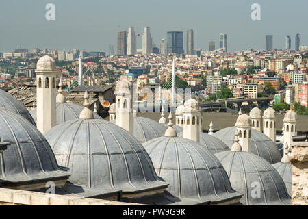 Stone chimneys of domed buildings with Golden Horn Metro Bridge in background, Istanbul, Turkey - Stock Photo