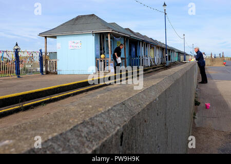 Sutton on Sea, Lincolnshire, UK. October 07, 2018. Locals approach holidaymakers to sign a petition against demolition of beach huts that have been a  - Stock Photo