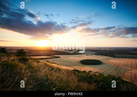 Sunset Looking over the village of Ham from Combe Gibbet, Berkshire. A dramatic sunset with stark contrast between cloud, land, and sun. - Stock Photo