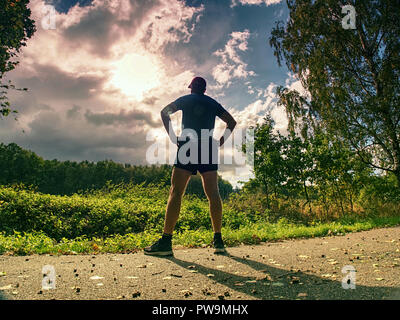 Jogging tall sports man in trees shadows with sun light behind him while wearing black yellow shorts and blue jogging attire