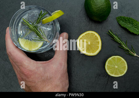 Hand holding glass of gin tonic with ice and lime on dark background - Stock Photo