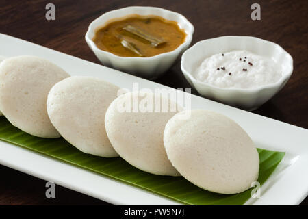 Fresh steamed Indian Idly (Idli / rice cake) arranged on banana leaf lined plate. Served with coconut chutney and sambar. Natural light used. - Stock Photo