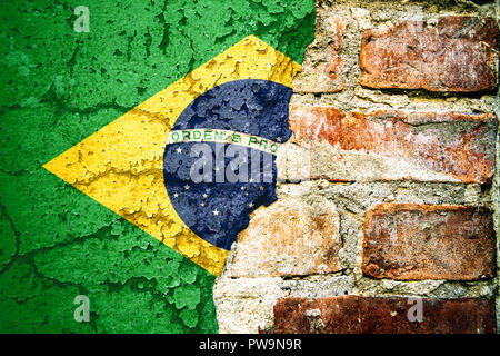 Brazil national flag painted on cracked divided peeling pain brick wall cement facade. Concept for Brazilian Portuguese language, culture and politica - Stock Photo