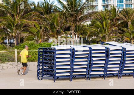 Miami Beach Florida South Beach sand public beach rental lounge chairs stacked man jogging jogger palm trees exercise fitness he - Stock Photo