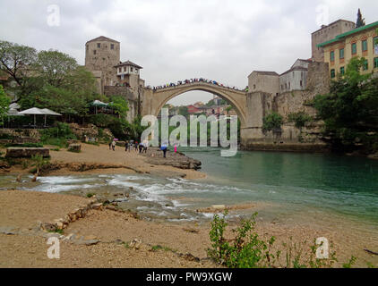The Old Bridge with many tourist over the Neretva River in the Historic Town of Mostar, Bosnia and Herzegovina, Balkans, Europe on May 1st, 2016 - Stock Photo