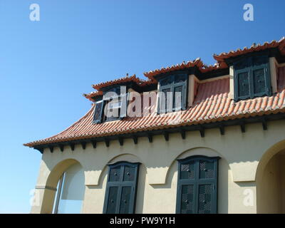 Mediterranean architecture, house with old black wooden window shutters and red tiled roof. - Stock Photo