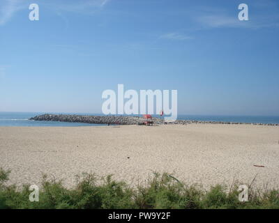 Sandy beach with green plants at the front and an old Baywatch post next to the stone mole - Stock Photo