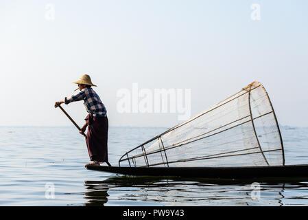 INLE LAKE, MYANMAR - FEBRUARY 15, 2014: Burmese fisherman on bamboo boat catching fish in traditional way with handmade net. Inle lake, Myanmar (Burma - Stock Photo