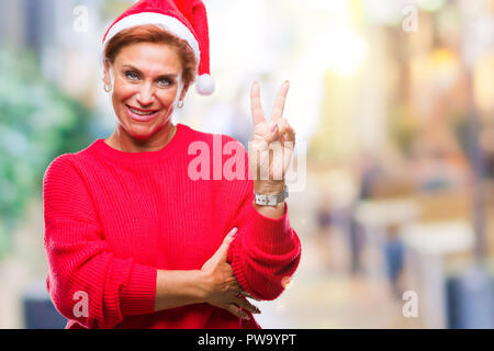 Atrractive senior caucasian redhead woman wearing christmas hat over isolated background smiling with happy face winking at the camera doing victory s - Stock Photo